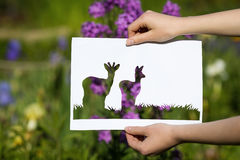 Holding papercut miniature 2 deers over blooming flowers Royalty Free Stock Photos