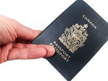 Holding a passport. A hand holding a Canadian passport, isolated on white Royalty Free Stock Photo