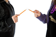 Holding pencils pointing at each other Royalty Free Stock Image
