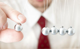 Holding a pendulum ball Stock Photos