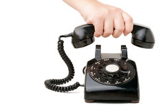 Holding the Phone. A hand  holding the handset of an old black vintage rotary style telephone isolated over white Stock Image