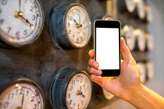 Holding phone with clocks on background Royalty Free Stock Images