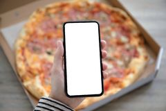 Holding phone with isolated screen above pizza box. Female hands holding phone with isolated screen above the pizza box stock images
