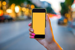 Holding phone on street background Royalty Free Stock Image