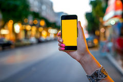 Holding phone on street background Royalty Free Stock Images