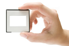 Holding a Picture Slide. Female hand holding a plastic picture slide frame. Isolated on a white background Royalty Free Stock Image