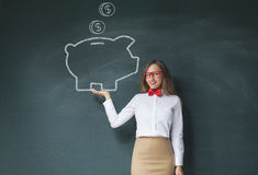 Holding piggy bank drawing front of blackboard stock image