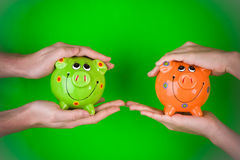 Holding piggy banks Royalty Free Stock Images