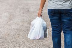 Holding Plastic Bags. Woman hold the plastic bags and walk on the street stock photography
