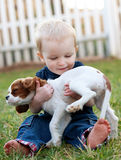 Holding puppy. Baby holding his new puppy Stock Image