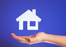 Holding Real Estate. Female hand holding a plastic icon of a house lit from below stock photo