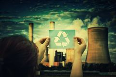 Holding recycle symbol. Woman holding a paper sheet with recycle symbol over factory pipe polluting air background, with smoke from chimneys going up in the sky royalty free stock images