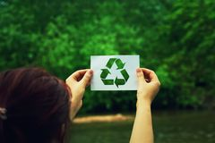 Holding recycle symbol. Woman holding a paper sheet with recycle symbol over green forest nature background. Ecology and greening concept Stock Images