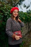Holding red handbag in red beret. Portrait of a young smiling woman in red beret holding a red handbag near a stone fence covered with vegetation royalty free stock photo