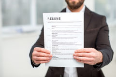 Holding resume paper. Man in the suit holding resume for job hiring. Close-up view focused on the paper royalty free stock image