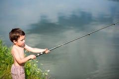 Child fishing. Child holding fishing rod, freshwater lake Stock Photos
