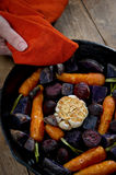 Holding Root Vegetables in a Cast Iron Skillet Stock Photo