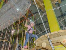 Holding the ropes in adventure Park the kid in the white helmet Royalty Free Stock Photography