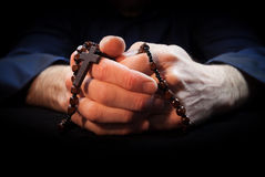 Praying Hands. Holding rosary beads and cross while praying Royalty Free Stock Images