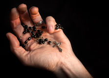 Time to reflect. Holding rosary beads and cross while praying Royalty Free Stock Photos