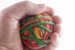 Holding Rubberband Ball. Closeup macro of a hand holding a rubberband ball Stock Photo