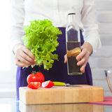 Holding a salad and olive oil bottle Royalty Free Stock Image