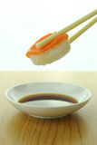 Holding salmon sushi roll with chopsticks and shoyu sauce Royalty Free Stock Photography
