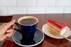 Holding-Schale der Frau Handheißer Kaffee mit dem Himbeerkremeis-Kuchen gedient auf Holztisch lizenzfreies stockbild