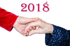 Holding senior woman`s hand, help concept 2018. Young woman is holding senior woman`s hand. New year helping concept Royalty Free Stock Images