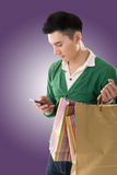 Holding shopping bags and using cellphone Stock Photography