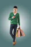 Holding shopping bags and using cellphone Stock Photos