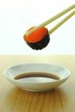 Holding shrimp eggs sushi roll with chopsticks and shoyu sauce Stock Photos