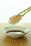 Holding shrimp sushi roll with chopsticks and shoyu sauce Royalty Free Stock Image