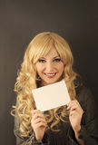 Holding sign. Beautiful young woman holding a blank piece of paper Stock Image
