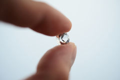 Holding a single diamond. Single diamond held together by the fingers. useful for showing the importance of a diamond Royalty Free Stock Images