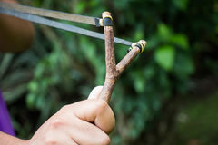Holding slingshot in hands against Stock Photos