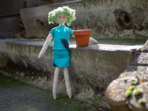 Springtime gardening, little rag doll girl with terra cotta clay pot royalty free stock photography