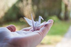 Holding a small paper crane in hand stock photo