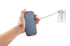 Holding Smart Phone And Tin Can Telephone I. Concept Image of female hand holding a smart phone connected to a tin can telephone Stock Image