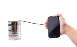 Holding Smart Phone And Tin Can Telephone II. Concept Image of female hand holding a smart phone connected to a tin can telephone Stock Image