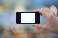 Holding Smartphone. Hand holding smartphone in front of a blurred background Royalty Free Stock Photography