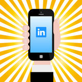 Holding smartphone with Linkedin logo Stock Photo