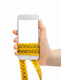 Holding the smartphone and measuring tape Royalty Free Stock Photos