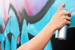 Holding spray paint on the wall graffiti Stock Photo