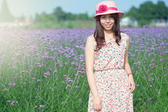 Holding a straw hat of the girl in flowers Stock Photos
