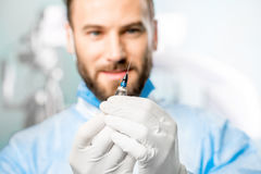 Holding surgical scissors. Surgeon holding small surgical scissors for eye operation in the operating room. Image with small deph of field focused on hands and Royalty Free Stock Images