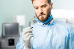 Holding surgical scissors. Surgeon holding small surgical scissors for eye operation in the operating room. Image with small deph of field focused on hands and Royalty Free Stock Photos