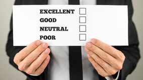 Holding survey check. Businessman holding a survey check with multiple choice check boxes for excellent - good - neutral - poor ratings stock photo