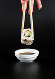 Holding sushi roll,Sushi roll on soy sauce,japanese food. Royalty Free Stock Image