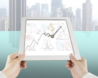 Holding tablet with business concept drawing and clock hands. City background Royalty Free Stock Photography